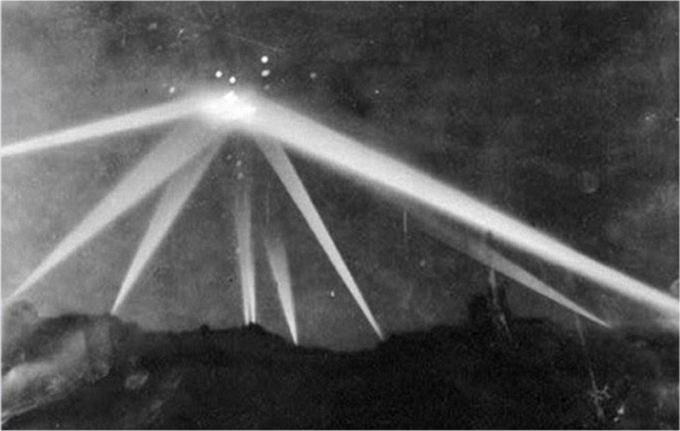Searchlights focus on an unidentified object over Los Angeles on February 25, 1942. The bright dots around the flashes are anti-aircraft shells exploding
