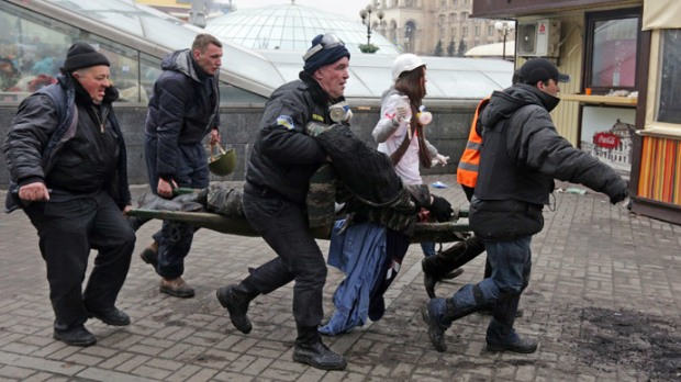A wounded protester is rushed to a vehicle following violence in Independence Square in Kiev February 20, 2014. (Reuters / Konstantin Chernichkin)