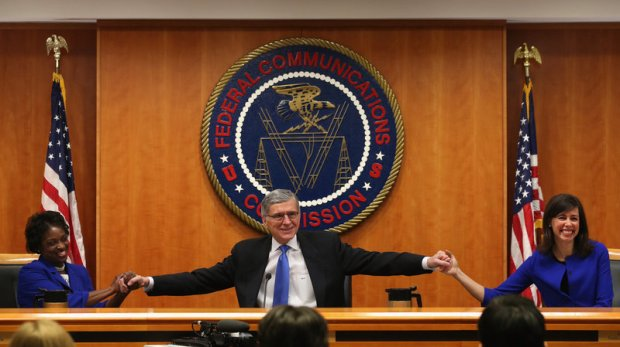 At the start of a meeting to decide the issue of net neutrality, Federal Communications Commission Chairman Tom Wheeler, center, holds hands with FCC Commissioners Mignon Clyburn, left, and Jessica Rosenworcel at the FCC headquarters Thursday.