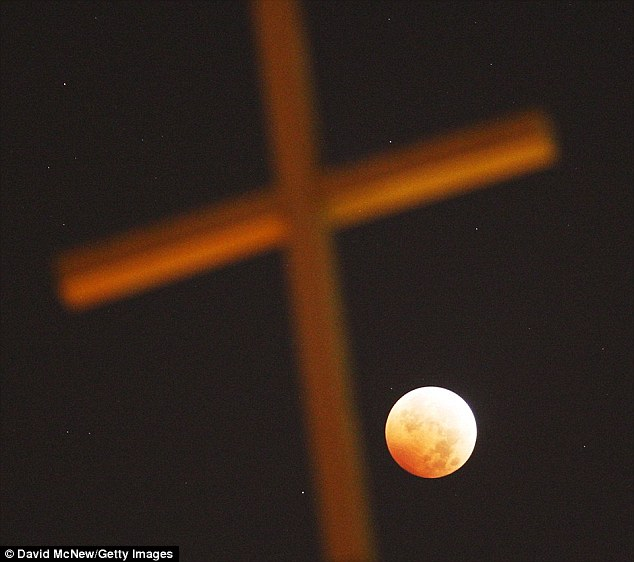 The strange celestial sight, which will be visible in the US, was predicted in the Bible and could hint at a world-changing event, such as the return of Christ, according to one pastor. This image shows the red moon over a church in LA during the last blood moon in October last year