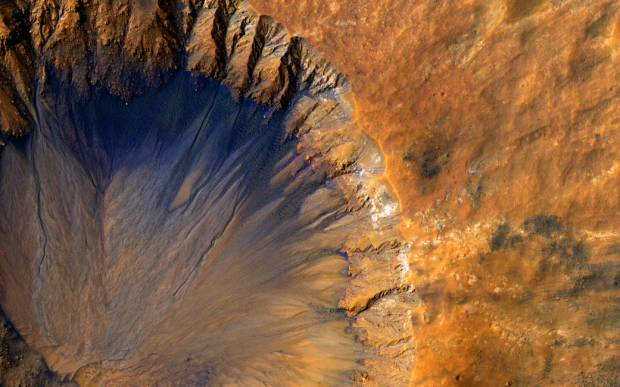 Closeup of Mars crater showing a quarter of the crater at left and surface at right