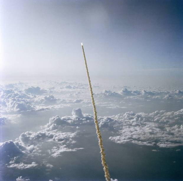 Space shuttle soars upward in sky above a layer of clouds after launch