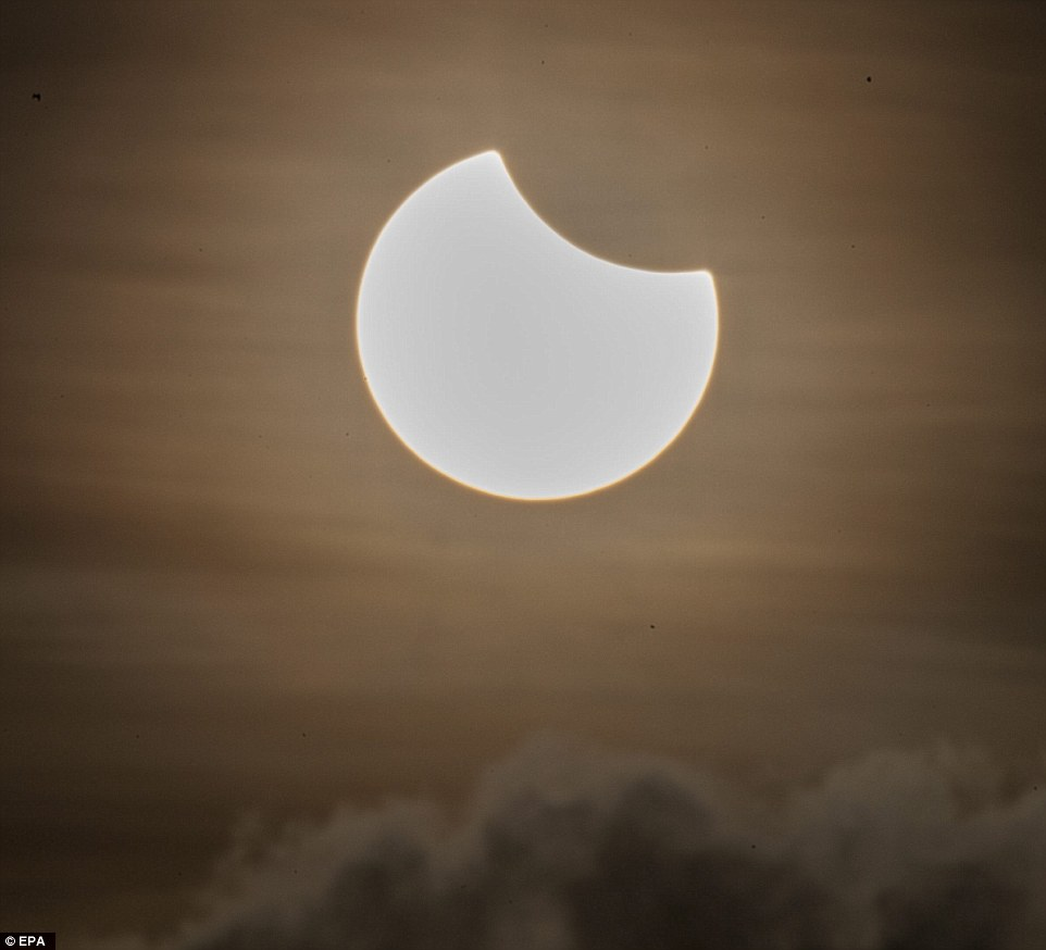 A partial solar eclipse is pictured above a cloud formation at dawn in Singapore on March 9. The eclipse was also visible around the region in Indonesia and Malaysia. However, only some parts of the country got to see the sun totally eclipsed by the moon, which happened almost immediately after the sun rose