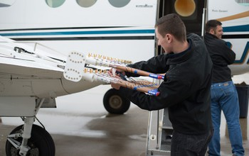 Pilots from Weather Modification, Inc., prepare the cloud seeding aircraft with seeding flares.
