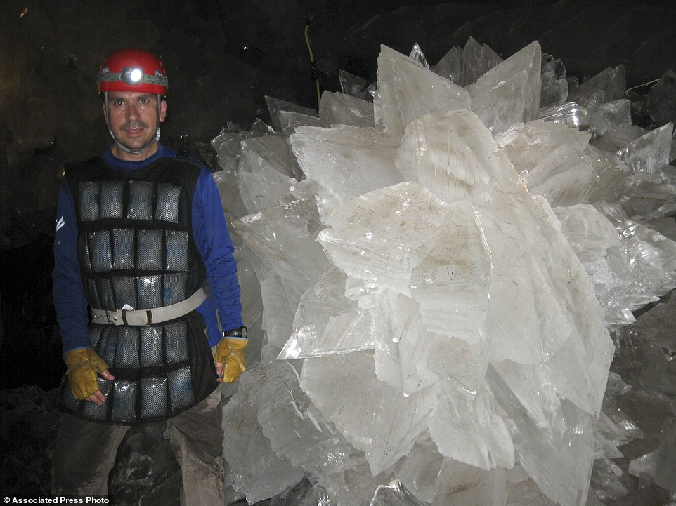 Mario Corsalini stands near to a gypsum rosette crystal, in the caves of which some were as large as cathedrals